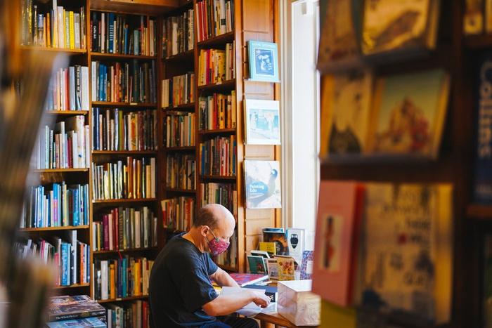 мужчина читает книгу, книжный магазин