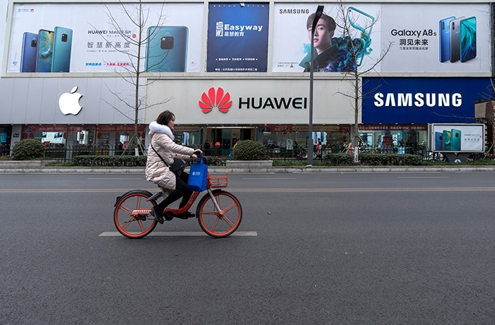 Девушка проезжает на велосипеде мимо магазинов смартфонов